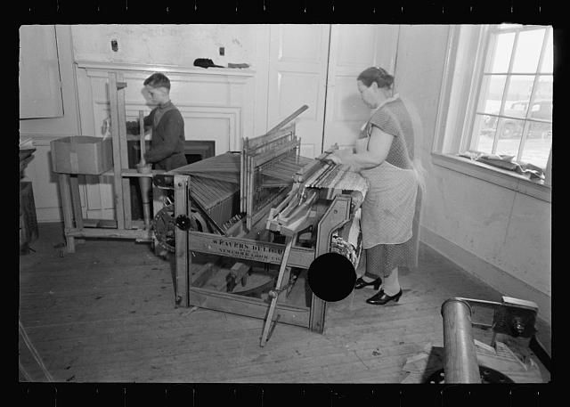 a woman weaving on an old loom
