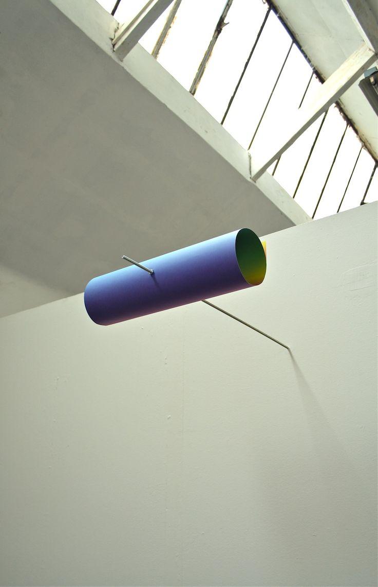 ARCOBALENO FRONTALE CLAUDIO CORFONE Arcobaleno frontale, 2013. Cartoncino arrotolato, vite, bulloni. Dimensioni ambientali 100x50x30 cm. Arcobaleno Frontale è una scultura dispositiva temporale.  Il gradient dei colori dell'arcobaleno sono stampati su cartoncino. Il cartoncino è arrotolato e conficcato in un asta filettata che a sua volta è conficcata nel muro ad una altezza di 2,40 cm circa.