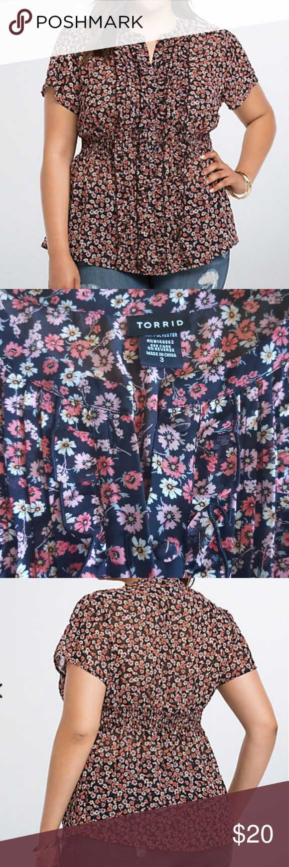 Torrid Floral?Chiffon Ruffle Top Tick, tick, tick, ka-bloom! This black and coral daisy print chiffon blouse has all the feminine features you could want in a romantic top. The ruffled button front paired with a smocked waist will have your figure looking amazing. torrid Tops