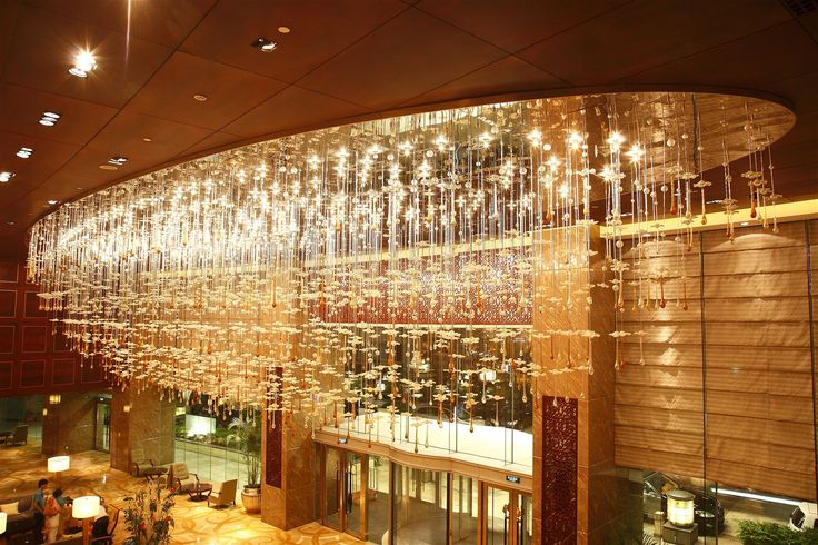 The modern lobby of the renowned Shangri-La Hotel Qing Dao received an opulent chandelier created from blown glass parts hand shaped into leaves, giving the hotel's public area an air of luxury and the highest level of service that awaits its guest. #light #lighting #design #designlighting #interior #crystal #chandelier #hospitality #hotel #lobby #hotellobby