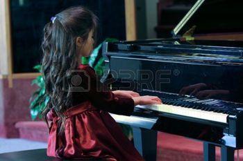 enfant qui joue: Un enfant joue piano à queue