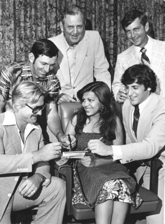 May 18, 1977: At a Birmingham event sponsored by the Myasthenia Gravis Association, Lulu Melwani collects autographs from, left to right, Birmingham Bulls hockey player Jim Turkiewicz, racecar driver Donnie Allison, University of Alabama football coach Paul Bryant, Auburn University football coach Doug Barfield and Chicago Bears running back Johnny Musso.