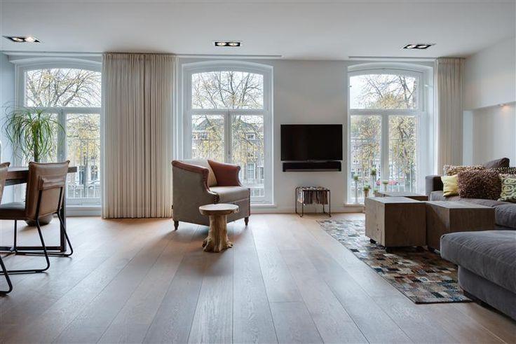 Stijlvolle woonkamer met grote raampartijen voorzien van Franse balkons.