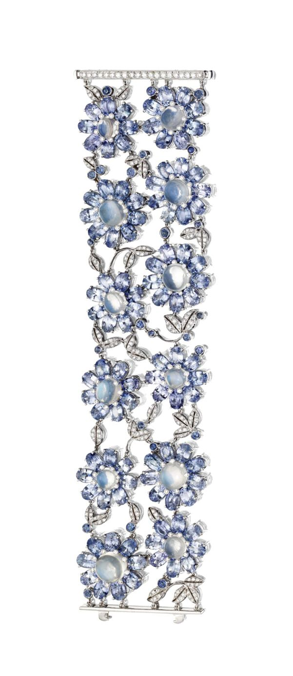 MOONSTONE, SAPPHIRE AND DIAMOND BRACELET.  Decorated in two rows with 12 flowerheads, each with a cabochon moonstone center, the petals set with oval sapphires, connected by meandering leaves and berries set with small round diamonds and sapphires, the total diamond weight approximately 3.00 carats, mounted in platinum