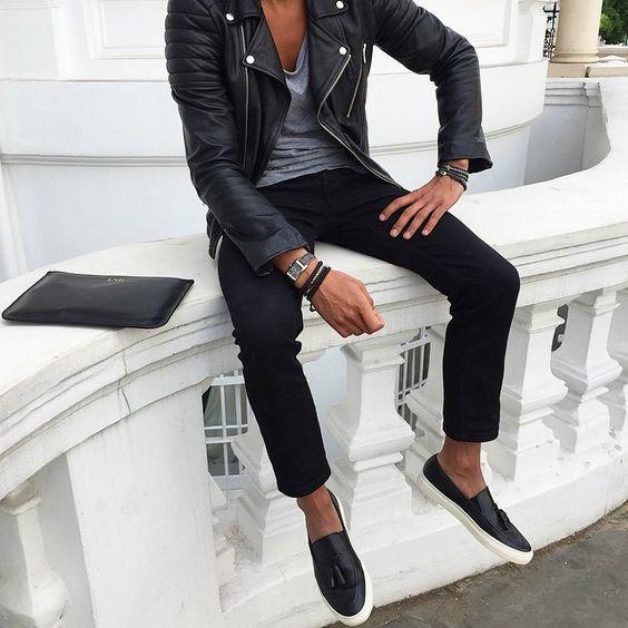 Acheter la tenue sur Lookastic: https://lookastic.fr/mode-homme/tenues/veste-motard-t-shirt-a-col-rond-pantalon-chino/18388   — Veste motard en cuir noir  — T-shirt à col rond gris  — Pochette en cuir noire  — Pantalon chino noir  — Mocassins à pampilles en cuir noirs