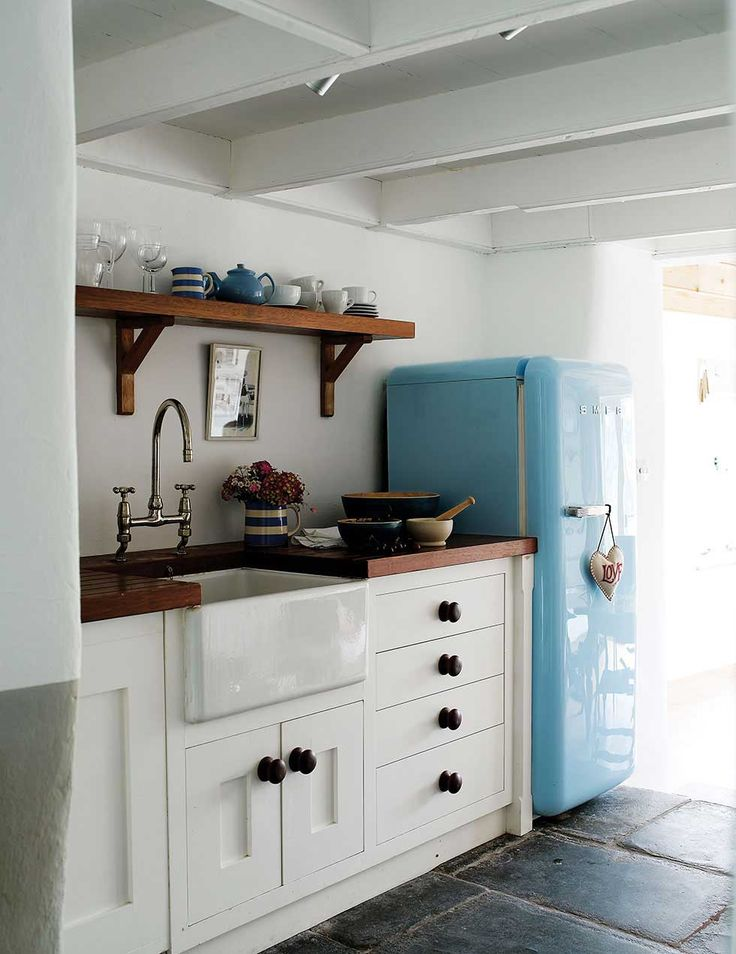 Small Constantine Kitchen With White Counters And Bright Blue Fridge
