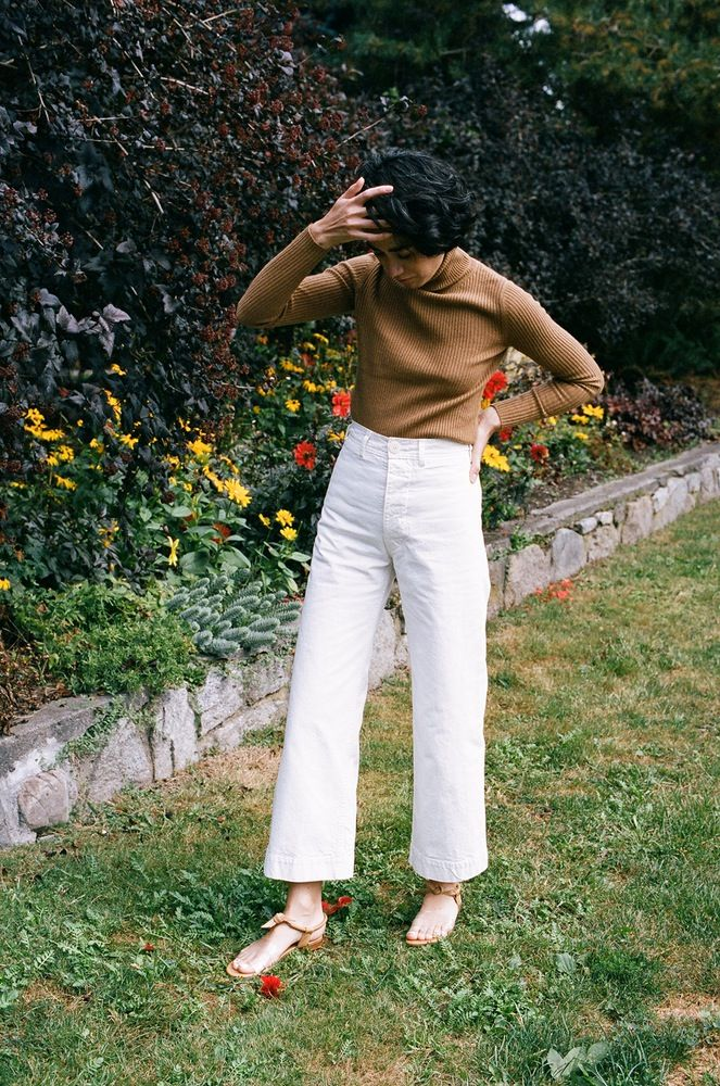 White high-waisted pants, sweater, sandals.