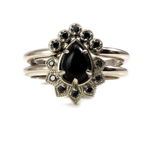 Pear Onyx and Black Diamond Gothic Cluster Engagement Ring with Crown Wedding Band - 14k Palladium White Gold  This wedding set in compact but dramatic. The engagement ring is set with a 5x7 pear shaped onyx cabochon, it weighs approximately 1 carat. The pear has a half halo of tiny pointed millgrained petals that are each set with a black diamond. The black diamonds on the engagement ring have a combined weight of approx. .07 carats. The crown wedding band has a V shape and fits with the…