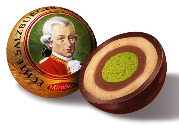 """The """"Original Salzburg Mozartkugeln"""" are still produced manually by the confectionery Fürst using the original recipe and technique: First, a ball of green pistachio marzipan covered in a layer of nougat is produced. This ball is placed on a small wooden stick and dunked in a dark chocolate coating. Next, the stick is placed vertically on a platform to allow the chocolate to harden. Finally, the stick is removed; the hole is filled with chocolate, the ball is wrapped in blue-silver foil by…"""