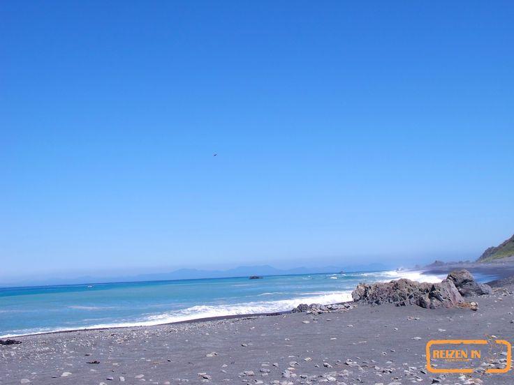 Strand net buiten Wellington, Nieuw-Zeeland. In de verte is het zuidereiland zichtbaar.
