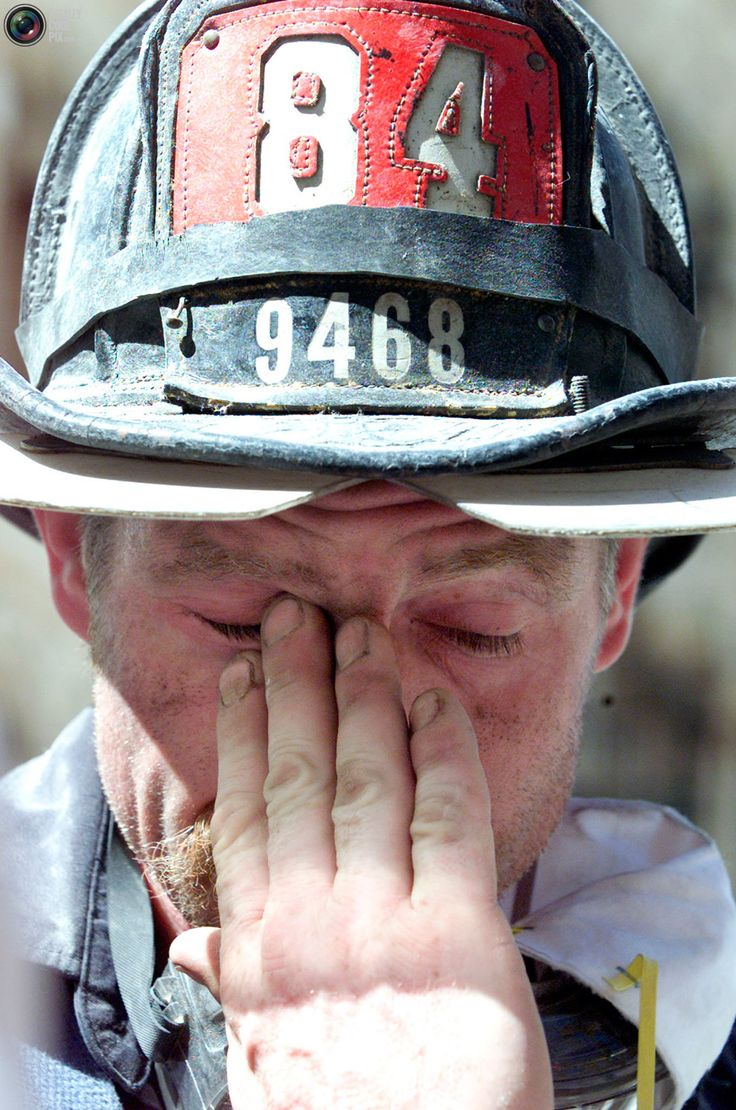 New York Firefighter John Cleary wipes the soot from his face while taking a break from rescue work at the World Trade Center in New York  on September 12, 2001. Clearly helped in the rescue of two trapped Port Authority workers, pulling the first from the rubble at one this morning and helping the second to safety at about four hours later.