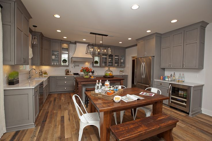 gray cabinets + white subway tile backsplash + white counters + rustic wood floors and table