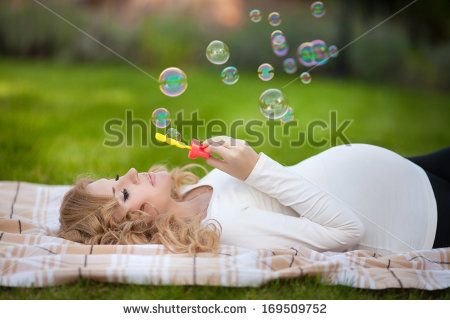 Young pregnant woman relaxing in park outdoors, healthy pregnancy. Happy pregnant woman with bubbles on nature. Beautiful pregnant woman holding her tummy.  - stock photo