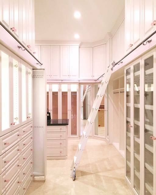 Featuring raised drawer panels, glass-framed cabinet doors & a ladder to reach upper storage, this dressing room utilizes all available space in style.  Learn more here: https://www.closetfactory.com/custom-closets/