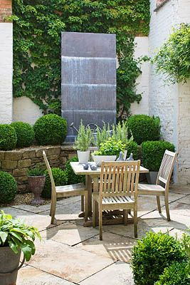 RICHARD CARNILL HOUSE, NOTTINGHAMSHIRE: COURTYARD GARDEN; SCULPTED LEAD PANEL CENTREPIECE, VINTAGE WATERING CANS, BOX BALLS AND CUBES. GARDEN DESIGN BY CHRIS MOSS