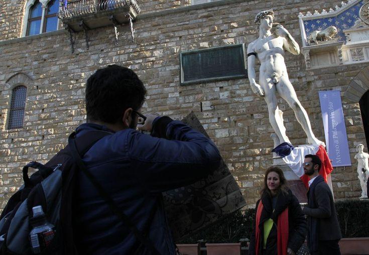 Il David di Michelangelo, in Piazza della Signoria a Firenze, con il  lutto al braccio per l'attentato di ieri al giornale satirico francese  Charlie Hebdo. Ai piedi della statua anche una bandiera della Francia  (Foto Cge Fotogiornalismo)