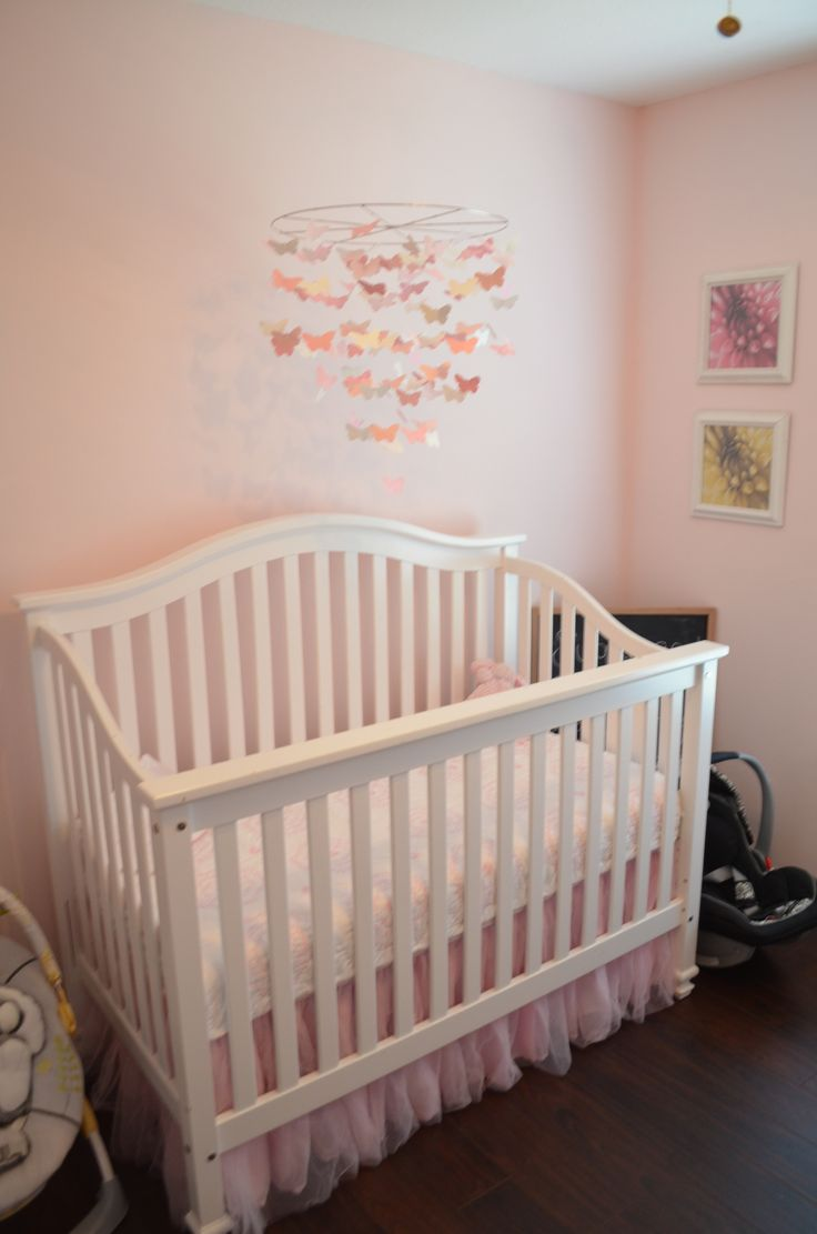 Crib & mobile setup with quilt, mobile and tulle crib skirt all from Pottery Barn Kids.