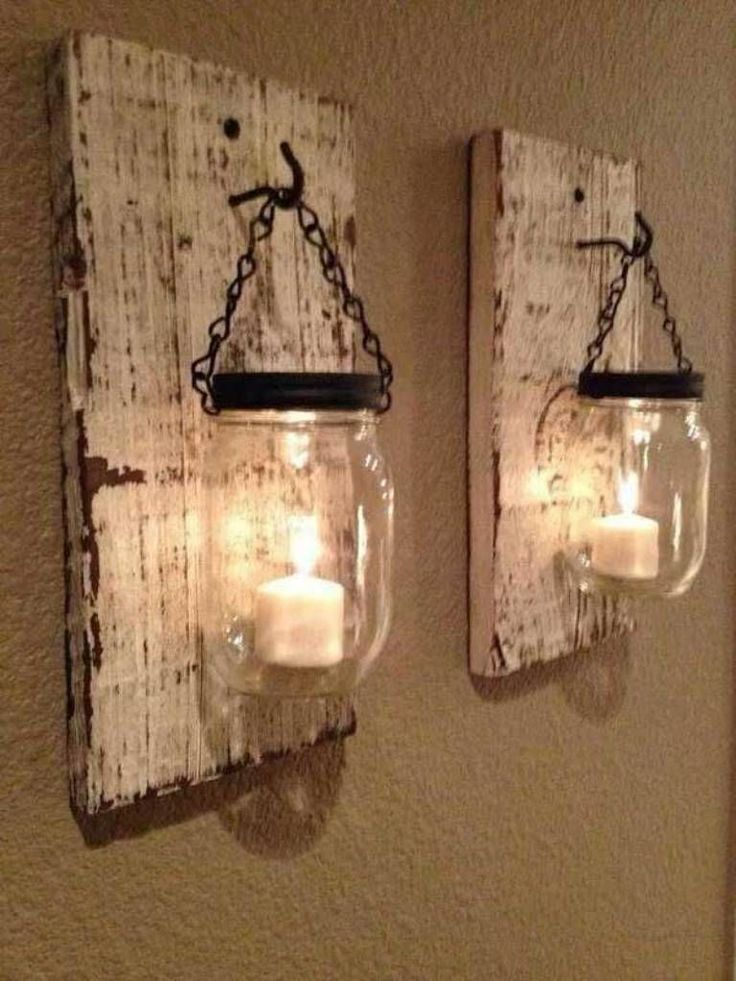 DIY farmhouse decoration lantern First, they spray painted the wood their desired color. Then, they hand painted the upper rims of their mason jars. They attached hooks to the pieces of wood and a short length of chain to the jars. After hanging the jars on the pieces of wood, all that was needed was two candles to bring these beautiful wall sconces to life.