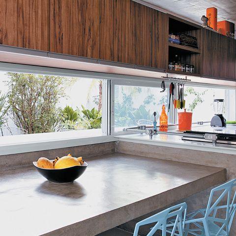 Na cozinha janela retangular para colocação de armário acima, vidro de correr já que do outro lado é uma varanda. Bancada de cimento
