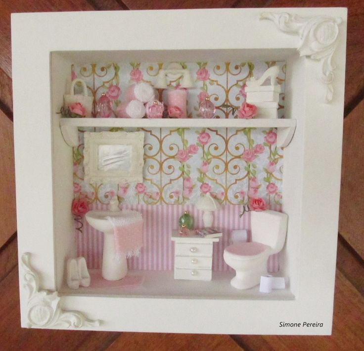 QUADRO COM VIDRO FRONTAL <br> <br>Quadro em mdf , pintado em branco, aplicação de scrap importado ( papel) listrado de rosa e arabescado formando um compose , peças de cerâmica branca , cômoda de madeira pintada de branco , espelho ,bolsa,caixa de sapato,sapato de salto alto de resina, toalhas feito à mão, miniaturas de perfume e papel higiênico. <br> <br>POR SER UM PRODUTO TOTALMENTE ARTESANAL , PODERÁ OCORRER ALGUMA ALTERAÇÃO NA DECORAÇÃO. <br> <br>Aceito encomenda com a cor de sua…