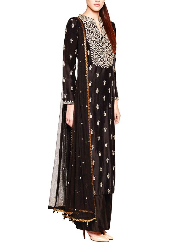 A black Anita Dongre Chanderi silk suit set cut beautifully and adorned with embellishments that make it fit for a festive occasion. The straight cut kurta features a band collar and full sleeves, with golden embroidery and sequin work in floral and leaf motifs. The set includes a pair of black palazzo pants that lend the outfit a contemporary edge.