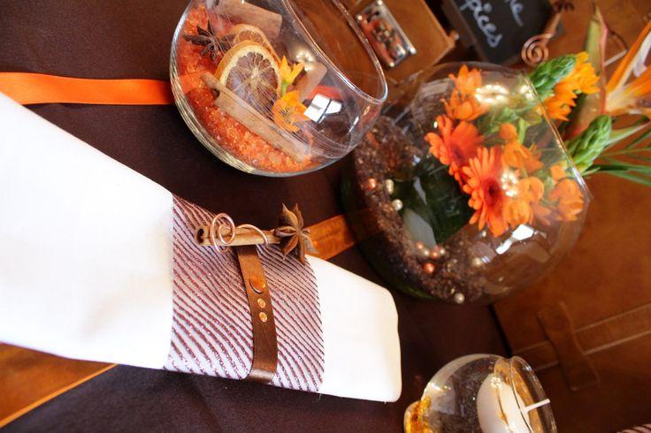 Ronds de serviette vagues pailletées, ruban satin marron et baton de canelle accompagnés de décorations de table fraiches et fleuries