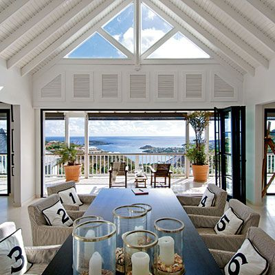 Haven on Earth    Classic architectural elements, such as a vaulted ceiling, mix with modern furnishings in this open living space. These homeowners carried a simple black-and-white palette throughout the house, relying on striped rugs and patterned fabrics to add variety and texture. The muted palette also helped ensure that the surrounding blue ocean and green palms stayed center stage.