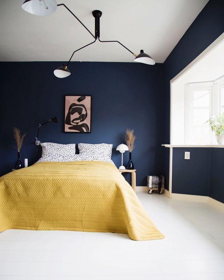 navy blue painted walls and mustard yellow linen duvet