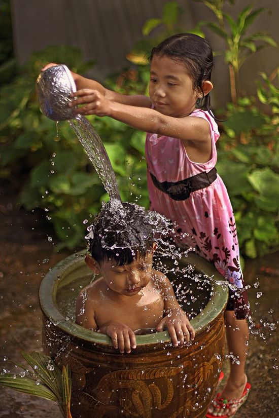INDONESIA. PRECIOUS sister bathing little brother.
