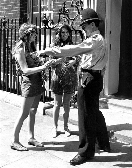 Two young women in hippie attire talk with a uniformed police officer outside of the government of Prime Minister Harold Wilson, 10 Downing Street, London, England, 1968, photographer unknown.
