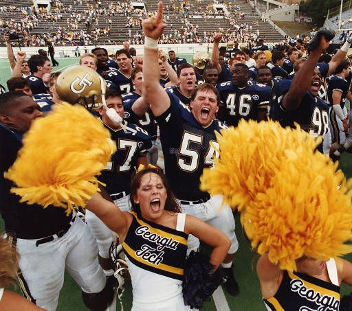 """Georgia Tech players and cheerleaders celebrate after beating UTC 44 to 9."" 1990. AJCP203-012g, Atlanta Journal-Constitution Photographic Archives. Special Collections and Archives, Georgia State University Library."