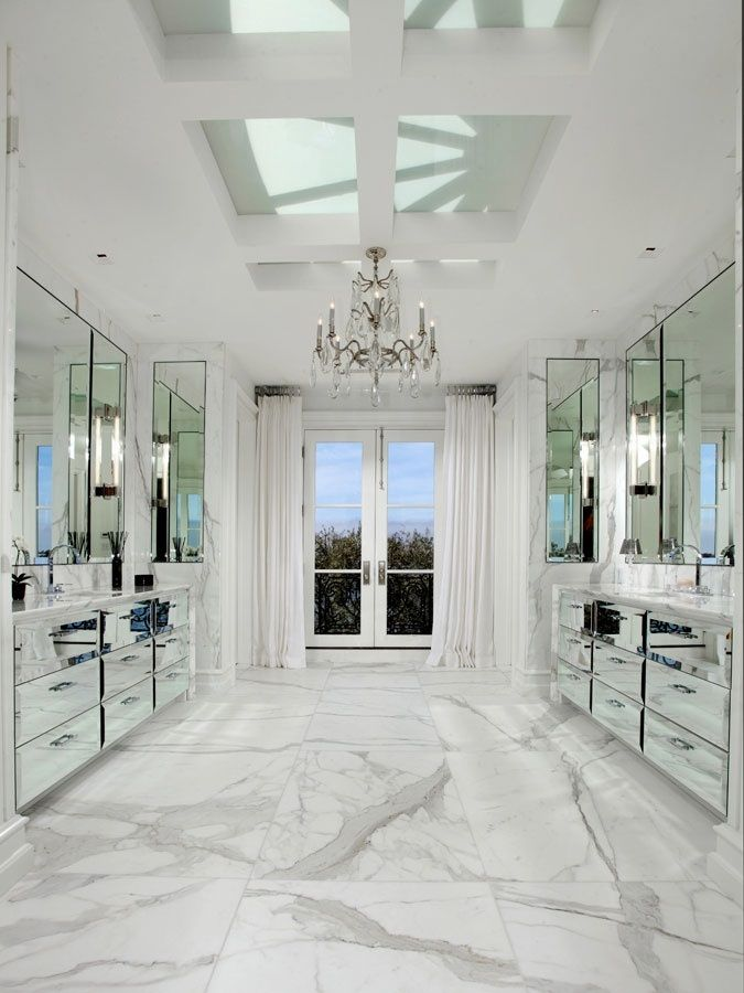 master bathroom with marble floor, mirrored cabinets and drawers, crystal chandelier, french doors and skylight