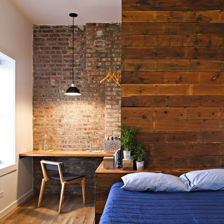 Exposed brick bedroom interior with small desk