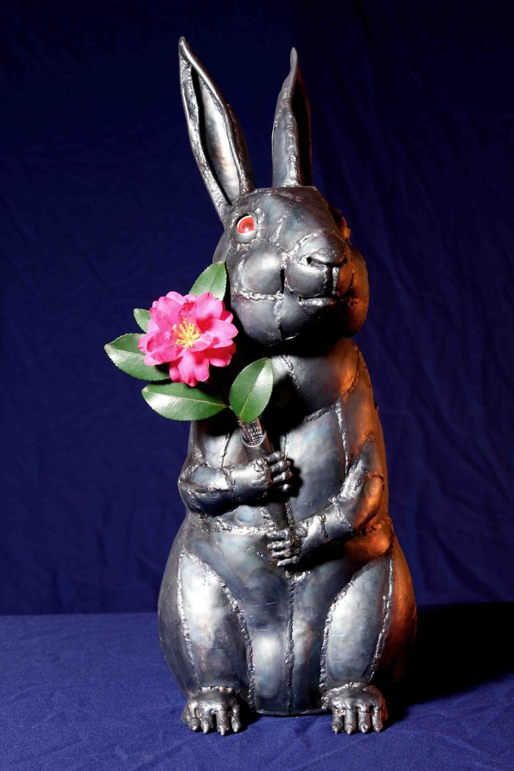 title :  A Rabbit Holding Flower   花を持つ兎  While rabbits in Japanese folk tales are typically wicked and cunning liars, this work depicts the delightful, gentle representation of rabbits.   In the world of the Tea Ceremony, utensils and images with rabbit motifs are often used, so this sculpture was produced to be used for tea ceremonies.  A vase that can be inserted into the rabbitユs chest for holding flowers adds a whimsical touch.