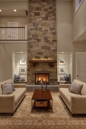 A Sky High Dry Stacked Stone Fireplace Is Matched By An Oriental Rug Wall Color Upholstery And Even Tiered Candles On The Mantle