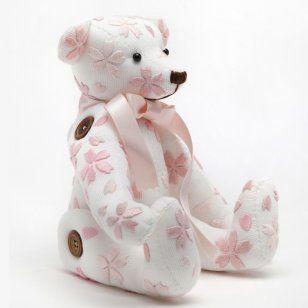 un superbe ours réalisé en tissu blanc, en couture avec des fleurs de cerisier roses brodées à la main. Réalisé pour le concours ours marie claire idées 2011
