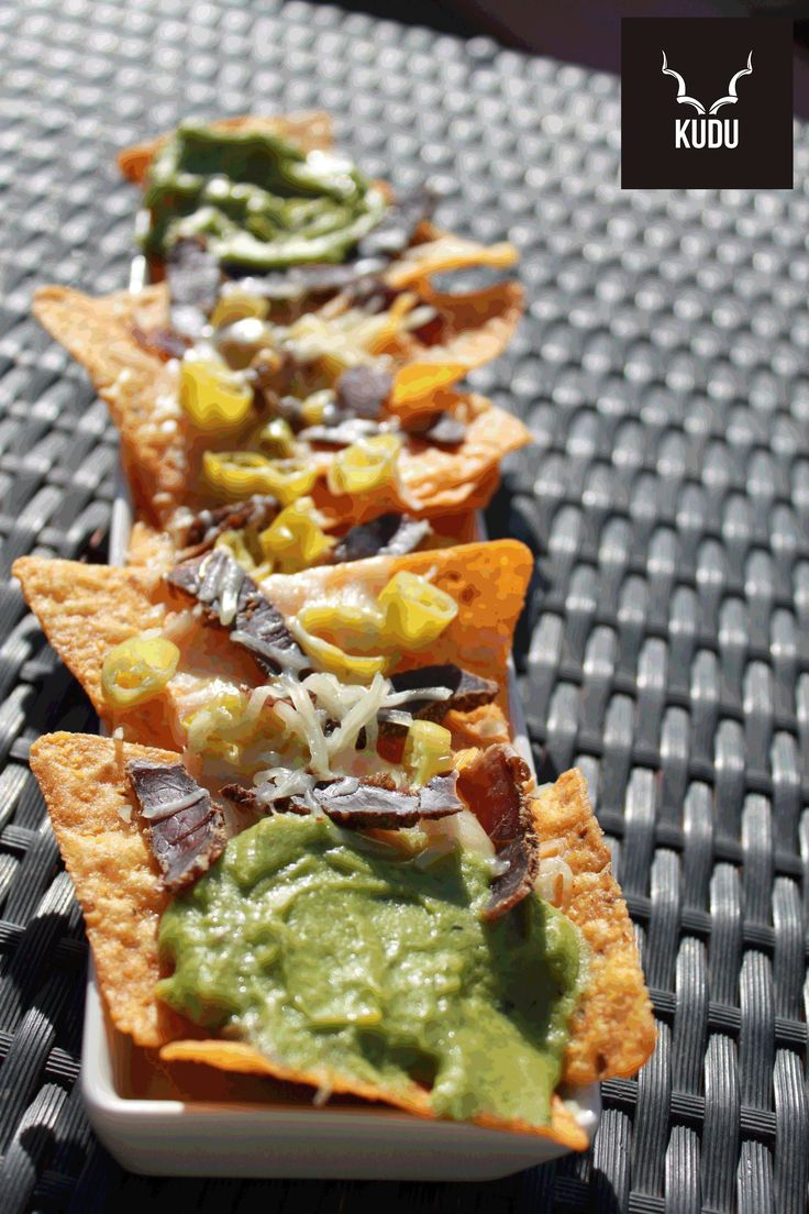 Nachos with biltong and jalapeños topped with cheddar cheese and guacamole
