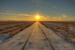 setting sun at the end of some railroad tracks in Saskatchewan Canada