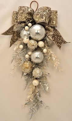 This stunning holiday swag is created with a sparkling combination of shiny silver and glittering silver, gold and platinum ornaments. Iced pine, glittered fern and shiny holly branches add a festive touch. Sparkling crystal stems add a textural accent. A rich platinum and silver brocade bow provides an elegant finishing touch to this timeless holiday swag.