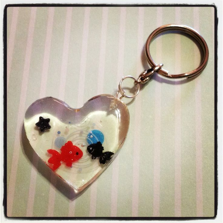 A red and black koi fish, or goldfish in a heart shaped resin keychain to hang all your keys from! A little black candy star sprinkle is also embedded in the resin, and this keychain is approx. 3cm wide and 3cm in length, and 0.5cm thick.  Given the preserving nature of the resin, the candy spr...