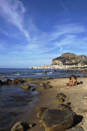 Couple on Beach, View to Cefalu with Rocca di Cefalu, Cefaly, Sicily, Italy