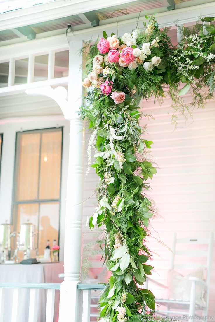 detail of porch entry arbor dressed with a loose and lush garland of lemon leaf, fern and weeping podocarpus, with clusters of coral charm peonies, white majolik spray roses, spirea branches, and peach, blush and pink roses.