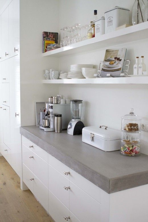White kitchen with open shelves and a cement countertop. Via vtwonen