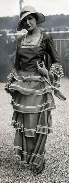 14-11-11  Damesmode. Modeshow op de renbaan van Longchamps. Lange japon met een rok met over elkaar liggende stroken en een hesje met vierkante hals. Longchamps, Frankrijk, 1930.