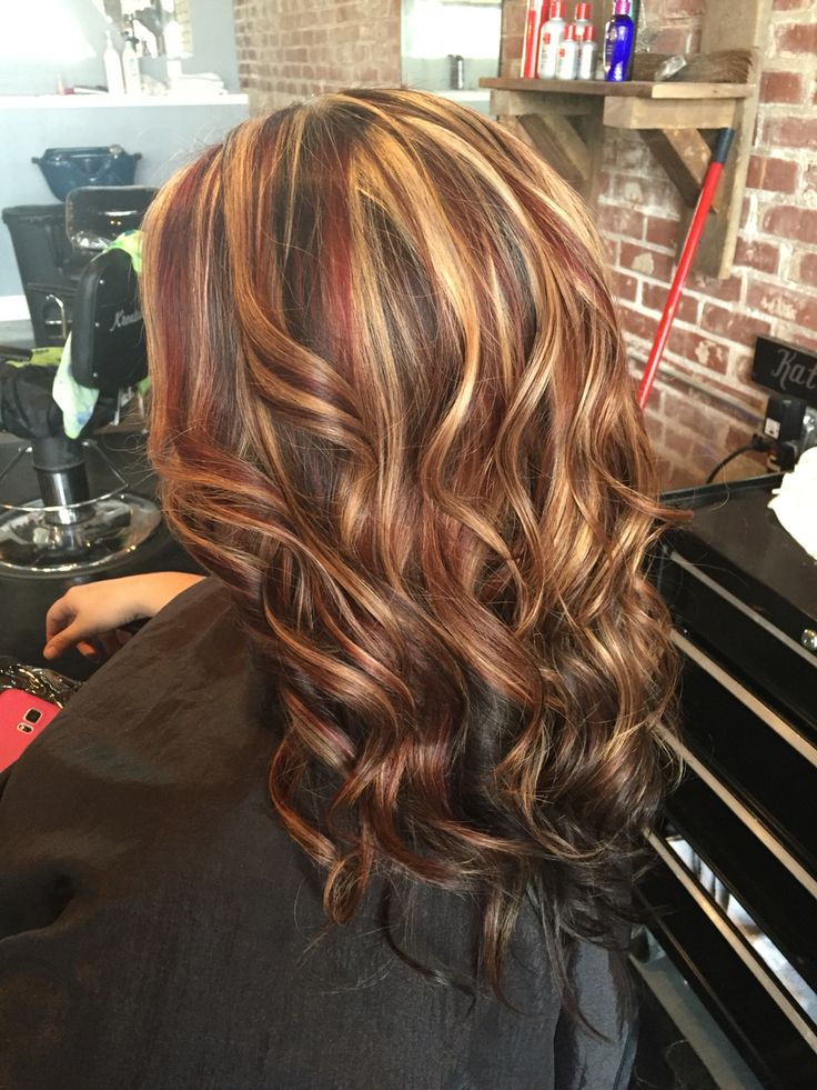 Dark brown underneath with white blonde highlights and dark brown low lights with fire hot red slices and chunky. Long layered haircut styled with curls #aloxxi #kreationsbykatie
