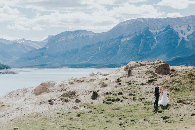 bride & groom strolling the shores of Abraham Lake near NOrdegg