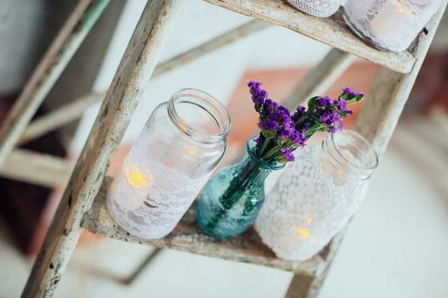 Lace jars as candles perched on vintage ladder with aqua bud vase of purple flower