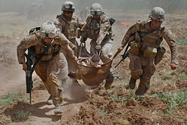 Afghanistan War August 21, 2010: US Marines carry a comrade wounded by an improvised explosive device (IED) to a waiting medevac helicopter, near the town of Marjah in Helmand Province