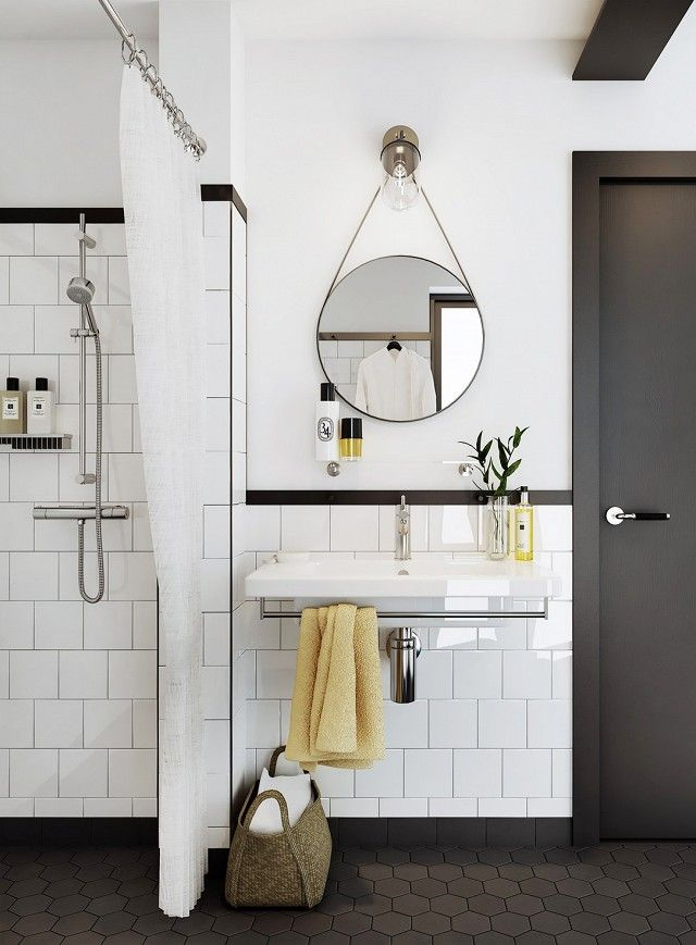 In this bathroom, another half wall is accented with a black border and paired with a black hexagonal tile floor. The styling is kept simple, with only a few yellow accents to add a pop of color....