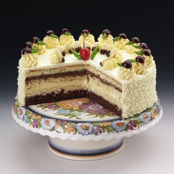 Tort Dziewczyna Jest Chłopak, poznajmy Dziewczynę. Ekskluzywny kremowy tort wykonany na bazie jasnego biszkoptu i kremu z masła, pasteryzowanych żółtek i wina Marshala. Niespotykany smak zawdzięcza warstwie czekolady z grylażem i przykwaskowej konfiturze z żurawin. Udekorowany białą czekoladą.